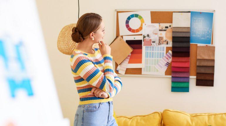 Kobieta analizuje moodboard wnętrza skomponowany na tablicy korkowej